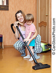 Family chores with vacuum cleaner in living room
