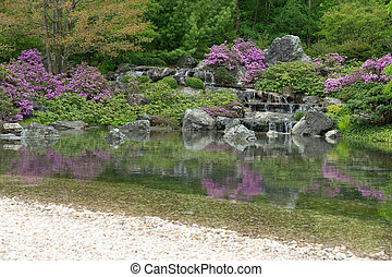 Blooming Japanese garden reflecting in pond - Blooming...