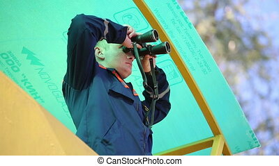 Rescuer on the tower looks in binoculars