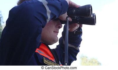 Rescuer looks in binoculars