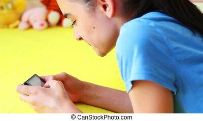 Girl messaging on smart phone - Preteen girl 12 years lying...