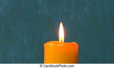 extinguishing yellow candle flame with brass bell tool