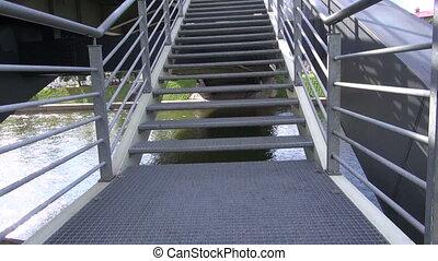 walking on metal bridge staircase - walking on big metallic...