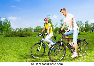 Two people on bikes - Two young people, man and woman riding...