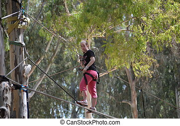 Young woman having fun on a rope park adventure course in a...