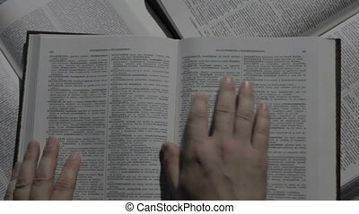 Hands over book while studying - Hands holding book turning...