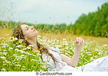 girl in a white sundress lies in camomile field