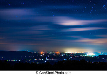 Stars and clouds move through the night sky over towns in...
