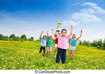 Kids with prize - Group of kids with lifted hands and with...