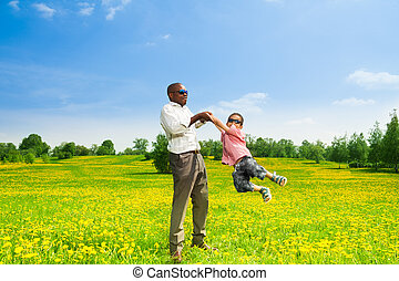 Rotating boy - Happy black father with his son rotating his...