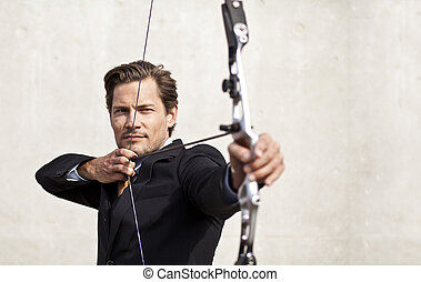 Businessman aiming bow and arrow - Businessman focusing on...