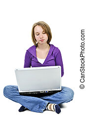 Girl with computer - Young girl sitting cross legged with...