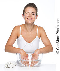 Relaxed young woman washing hands in glass bowl with water