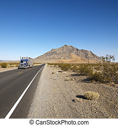 Truck on desert road. - Tractor trailer driving on desert...