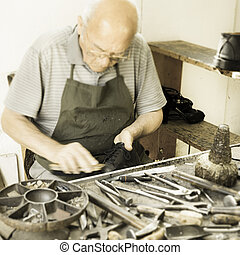 Shoemaker - Old shoemaker intent to shine a shoe
