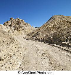 Death Valley road. - Dirt road through barren landscape in...