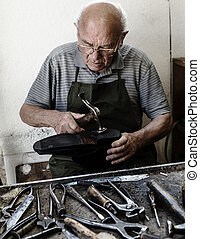 Shoemaker - Old shoemaker adjusts the sole of a shoe