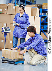 two chinese workers in warehouse - two young chinese workers...