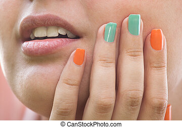 Close-up Of Woman Hands On Cheek And Colorful Nail Varnish
