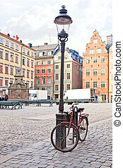 Bicycle near a lamppost - City landscape. Houses and streets...