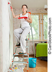 woman makes repairs at home - Happy mature woman makes...
