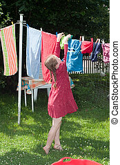 young girl hanging cloth to dry