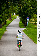 boy riding bicycle on rural road - boy on small road riding...