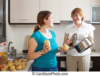 Mature woman and  daughter cooking  in kitchen