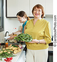 mature woman and adult daughter cooking vegetables -...