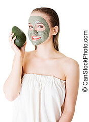 Beautiful woman with green avocado clay facial mask,...
