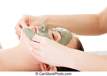 Beauty treatment in spa salon. Woman with facial clay mask....