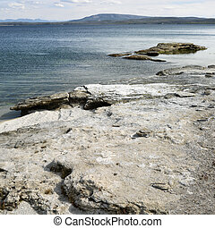 Yellowstone National Park. - Rocky shoreline at Yellowstone...