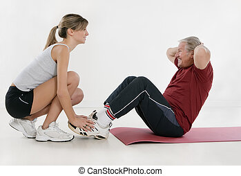 fitness - young personal trainer and senior adult exercising...