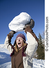 snowball - front view of young woman throwing huge snowball....