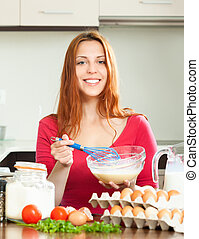 woman whipping dough in bowl - Smiling woman whipping dough...