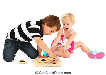 Adorable Caucasian brother and sister sitting on floor with...
