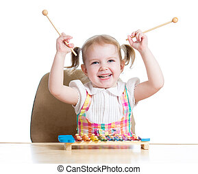 cheerful child girl playing with musical toy