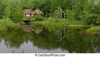 Traditional farmers house reflecting in a pond in open air...