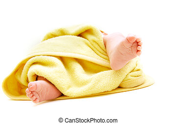 tiny baby\'s feet in towel over white