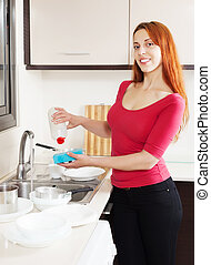 Happy housewife  washing plates with  detergent