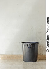 black garbage can with grunge wall. - Black garbage can with...