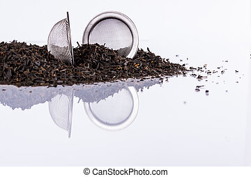 Black tea and tea strainer on white background