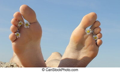 Happy Feet with Chamomile - Feet of a young man lying on a...