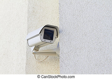 security - A new security camera is mounted on a wall.