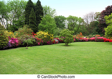 Beautiful manicured lawn in a summer garden with a border of...