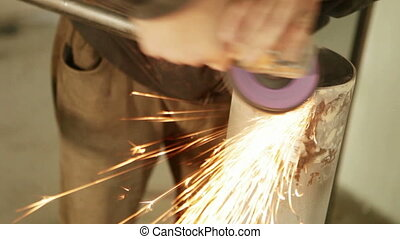 Grinding metal railing A man polishes stainless steel...