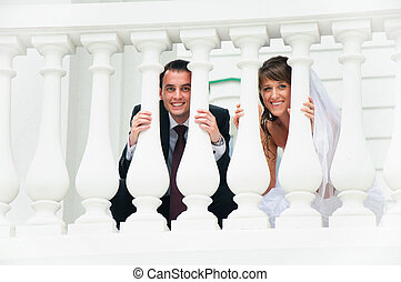 wedding couple smile and look out from white baluster. Love...