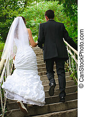 wedding couple walk up to stairs and holding hands backview