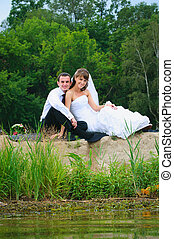 loving wedding couple sitting on sand near water