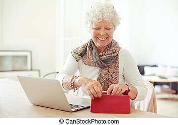 Cheerful Old Woman Getting Something from Her Wallet